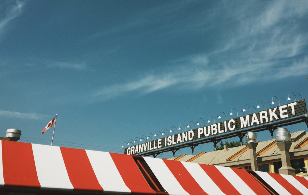 Image of Granville Island Public Market red and white striped awning and the Market sign on the roof