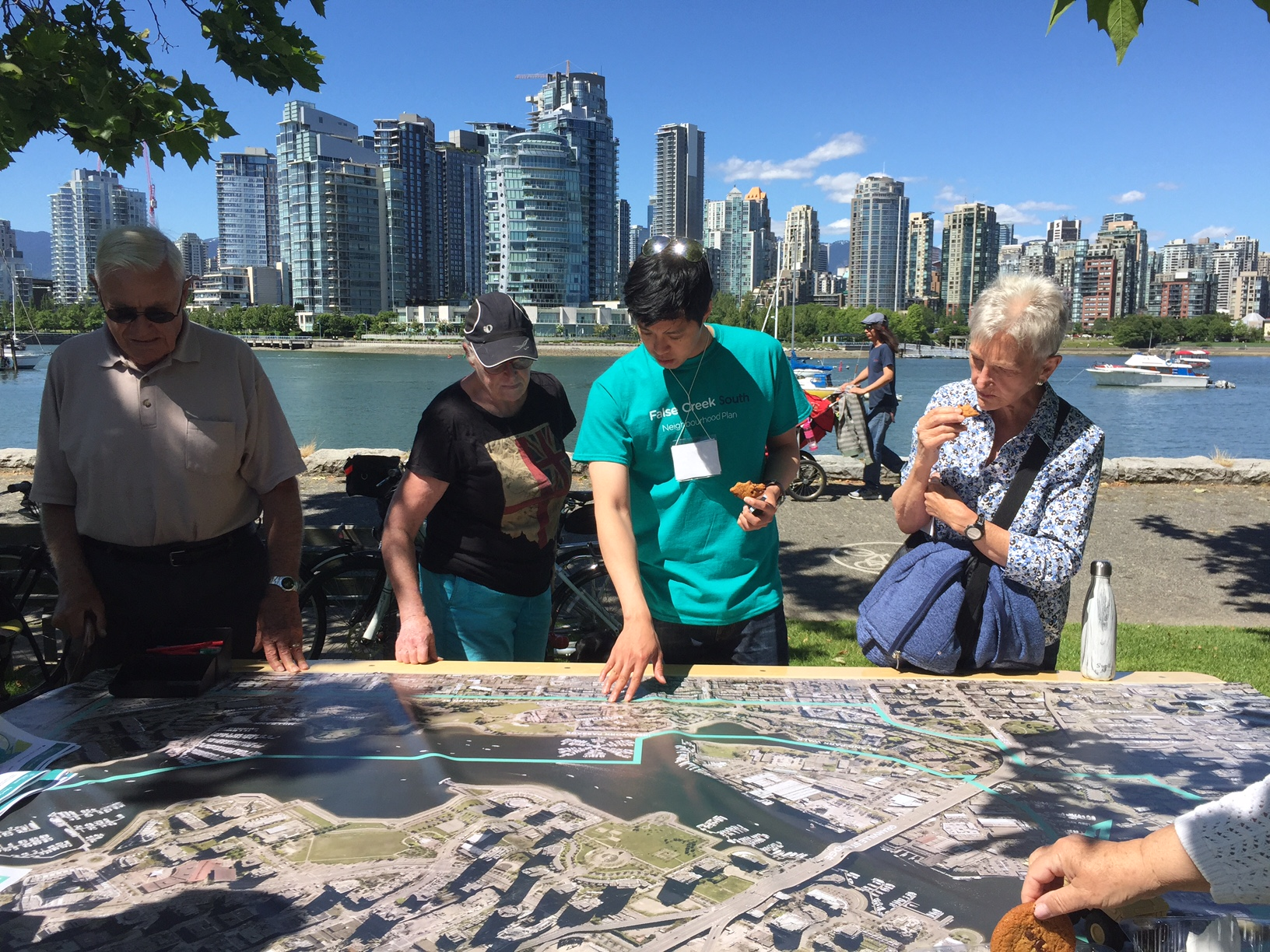 community members examine a very large map on a table with City staff